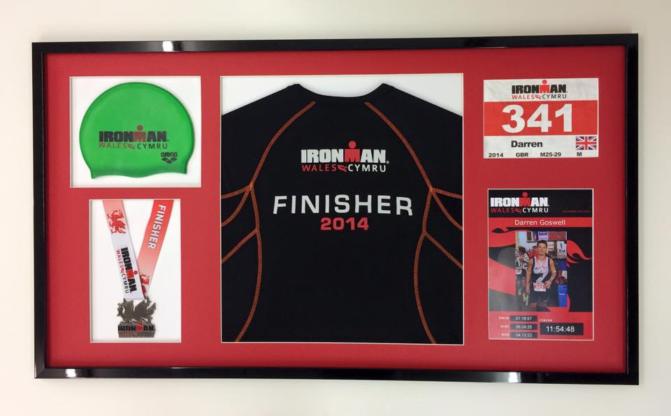 Ironman challenge memorabilia in a black frame with red mount