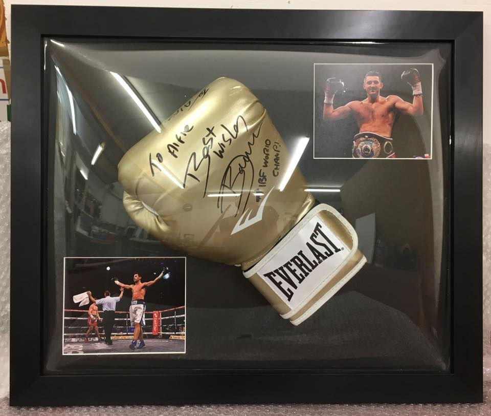 Golden boxing mit in a black frame with two pictures of the boxer in the ring